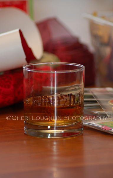 Buffalo Trace Bourbon in Buffalo Trace glass on the rocks, holiday wrapping paper in the background. - photo by Mixologist Cheri Loughlin, The Intoxicologist