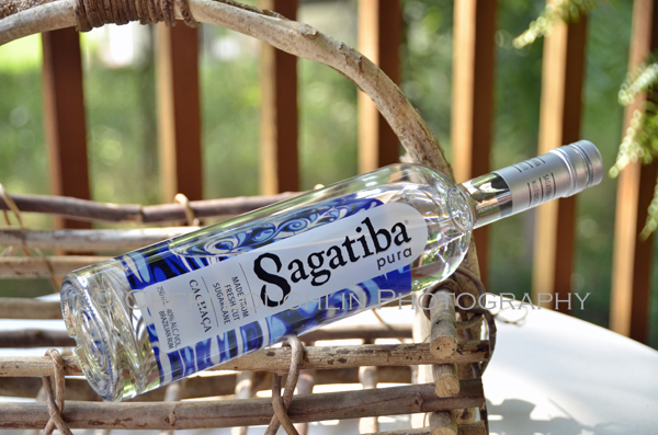 Sagatiba Cachaca Bottle 018 shown on side laying on basket. - photo by Mixologist Cheri Loughlin, The Intoxicologist
