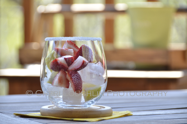 Layered ice, quartered fresh strawberries and lemon slices in glass with sugared rim ~ makes a beautiful garnished glass! – recipe and photo by Mixologist Cheri Loughlin, The Intoxicologist
